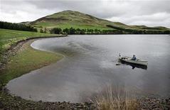 <p>Рыбак плывет на маленькой лодке в водохранилище Гленкорс в Шотландии 19 мая 2006 года. Экстренным службам пришлось спасать мужчину, путешествовавшего на лодке, после того, как у него закончился бензин, пока он кружил вокруг небольшого острова в устье Темзы. REUTERS/David Moir</p>