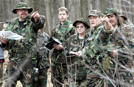 Michigan Volunteer Militia member Ken Fellows (L) points as he talks about using a compass during a militia ''survival in the wilderness'' training event at a state park in Brighton, Michigan in this photo taken April 3, 2010. REUTERS/Rebecca Cook