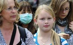 <p>A girl wears a face mask as she walks along Whitehall in London, July 30, 2009. REUTERS/Toby Melville</p>