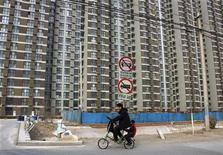 <p>Мужчина и мальчик проезжают на велосипеде мимо жилого здания в окрестностях Пекина 23 марта 2010 года. Власти китайской столицы запретили покупать больше двух квартир на семью в своем городе, пытаясь ограничить яростную спекуляцию жильем. REUTERS/David Gray</p>