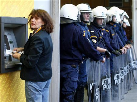 A woman makes a transaction at an automated teller machine during a rally against austerity measures outside Greece's Finance Ministry in Athens, April 29, 2010. REUTERS/John Kolesidis