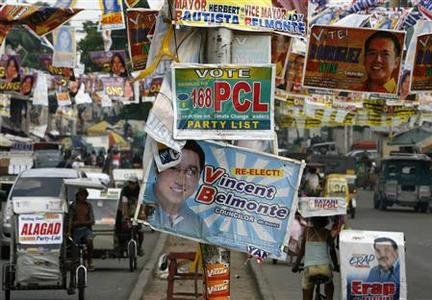 Motorists drive past election posters hanging along a road in Quezon City in Metro Manila May 5, 2010. REUTERS/Cheryl Ravelo