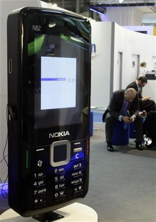 A man rests near a Nokia display at the Mobile World Congress in Barcelona February 17, 2010 file photo. REUTERS/Albert Gea