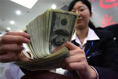 <p>A Chinese bank employee counts U.S. currency notes at a local bank in Nanjing, capital of east China's Jiangsu province April 4, 2006. REUTERS/Stringer</p>