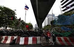 """<p>""""Краснорубашечники"""" сидят рядом с баррикадами в центре Бангкока 11 мая 2010 года. Армия Таиланда предупредила, что может использовать силу для разгона демонстрантов-""""краснорубашечников"""", обосновавшихся в центре Бангкока. REUTERS/Jerry Lampen</p>"""