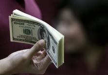 <p>Служащая пункта обмена валют в Джакарте передает деньги клиенту 28 октября 2008 года.Всем, кто сталкивается в России с должностными лицами, приходится давать взятки, убеждено свыше половины жителей РФ, показал опрос Левада-центра. REUTERS/Enny Nuraheni</p>