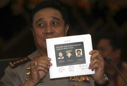 Indonesia's National Police Chief Bambang Hendarso Danuri shows pictures of suspects, involved in funding militant training activities in Aceh, to reporters at police headquarters in Jakarta, May 14, 2010. REUTERS/Dadang Tri