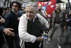 <p>Uruguayan President Jose Mujica arrives for the celebration of the Worker's Day carrying his pet dog Manuela, May 1, 2010. REUTERS/Andres Stapff</p>