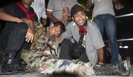 <p>Военный советник тайландской оппозиции Каттия Савасдипол (в центре) лежит на земеле после ранения во время интервью с журналистами в Бангкоке 13 мая 2010 года. Бывший военнослужащий армии Таиланда и советник антиправительственных демонстрантов Каттия Савасдипол скончался в понедельник от полученных ранений, сообщил главврач больницы, где он находился. REUTERS/Cyrille Andres</p>