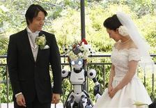 """<p>Un robot llamado """"I-Fairy"""" actúa como sacerdorte en la boda de Tomohiro Shibata y Satoko Inoue, en Tokio. Mayo 16 2010. El novio lucía elegante, su novia resplandecía en blanco, pero toda la atención en este matrimonio japonés estaba en el sacerdote; un robot de cuatro pies de alto con coloridos y brillantes ojos llamado i-Fairy. REUTERS/Yuriko Nakao</p>"""