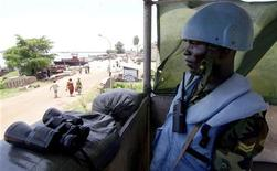 <p>A Ghanaian peacekeeper from United Nations Mission in the Democratic Republic of Congo (MONUC) stands guard in front of the local port where rebels came onshore on Easter Sunday as part of an attack that took over the airport in the Democratic Republic of Congo's northern Equateur province of Mbandaka, April 12, 2010. REUTERS/Katrina Manson</p>
