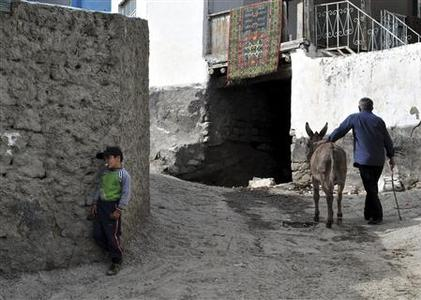 Local residents are seen along a street in the village of Balakhani, 150 km (90 miles) southwest of Dagestan's capital Makhachkala, May 12, 2010. REUTERS/Sergei Rasulov/News Team