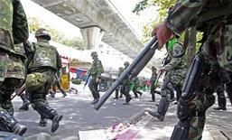 """<p>Таиландские солдаты патрулируют Бангкок 19 мая 2010 года. Четыре лидера таиландских антиправительственных демонстрантов сдались полиции после того, как войска пошли на штурм лагеря """"красных рубашек"""" в центре Бангкока. REUTERS/Sukree Sukplang</p>"""