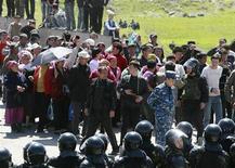 <p>Сотрудники ОМОНА сдерживают людей, собравшихся в поселении Нижняя Алаарча неподалеку от Бишкека, 20 апреля 2010 года. На юге Киргизии в среду вспыхнули волнения на национальной почве - в столкновениях между киргизами и узбеками в Джалалабаде погибли двое и более 70 пострадали, а власти и общественность пытаются снять напряженность, грозящую перерасти в кровавый конфликт. REUTERS/Vladimir Pirogov</p>