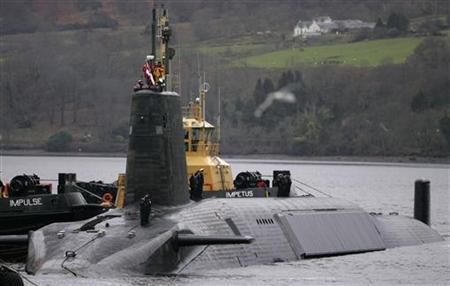 Crew from HMS Vengeance, a British Royal Navy Vanguard class Trident Ballistic Missile Submarine, stand on their vessel as they return along the Clyde river to the Faslane naval base near Glasgow, Scotland December 4, 2006. REUTERS/David Moir