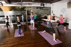 <p>A class in Warrior Two pose at the hot yoga room at Crunch, New York City, in an undated photo. REUTERS/Crunch/Handout</p>