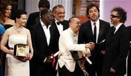 """<p>Diretor Apichatpong Weerasethakul (centro) é cumprimentado pelo júri presidente Tim Burton (dir) ao lado dos atores Javier Bardem (2o à dir) e Juliette Binoche (esq) ao vencerem o prêmio de melhor filme por """"Uncle Boonmee Who Can Recall his Past Lives"""" no Festival de Cannes. 23/05/2010 REUTERS/Eric Gaillard</p>"""
