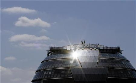 Workers install photovoltaic solar panels on the roof of City Hall in London May 23, 2007. REUTERS/Alessia Pierdomenico