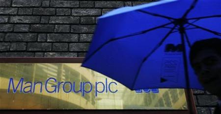 A man passes a sign for Man Group hedge fund firm in London November 6, 2008. REUTERS/Luke MacGregor