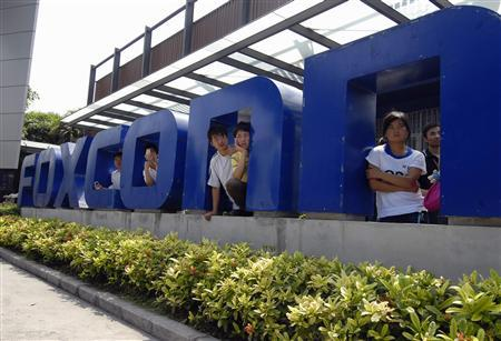 Workers stand at the gate of a Foxconn factory in the township of Longhua in Shenzhen, Guangdong province May 26, 2010. REUTERS/Stringer
