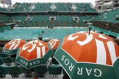 """<p>Зрители сидят под зонтами во время дождя, прервавшего """"Ролан Гаррос"""" в Париже 27 мая 2010 года. Проливной дождь заставил организаторов Открытого чемпионата Франции по теннису """"Ролан Гаррос"""" отложить начало матчей в четверг. REUTERS/Regis Duvignau</p>"""
