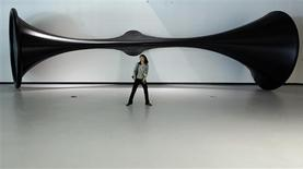 <p>A woman walks in front of a creation by Indian sculptor Anish Kapoor at the Maxxi, Italy's first national museum of contemporary art designed by Zaha Hadid, in Rome May 27, 2010. REUTERS/Stefano Rellandini</p>