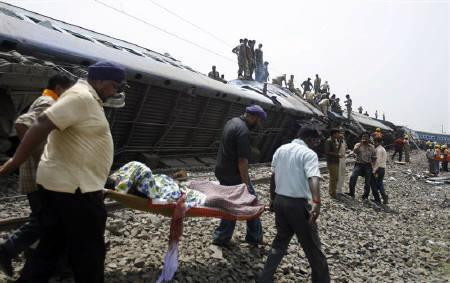 Rescue workers carry an injured passenger as others gather near the overturned carriages of a train at the site of an accident at Jhargram area in West Bengal May 28, 2010. REUTERS/Parth Sanyal