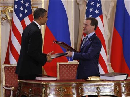 President Barack Obama ( L) and Russian President Dmitry Medvedev (R) exchange documents after signing the new Strategic Arms Reduction Treaty (START II) at Prague Castle in Prague, April 8, 2010. REUTERS/Jason Reed