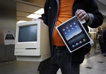 Hans-Henrik Duessel from Svendborg, Denmark, displays his old Apple Macintosh Classic computer from 1990 beside his newly purchased Apple iPad after being among the first to purchase the new device during an iPad launch event at the Apple retail store in Hamburg May 28, 2010. REUTERS/Christian Charisius