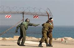 <p>Израильские солдаты эвакуируют раненого товарища в госпиталь в городе Хайфа 31 мая 2010 года. Как минимум 15 человек погибли в результате перехвата израильскими военными кораблями конвоя судов с гуманитарной помощью, направлявшихся в сектор Газа, сообщил частный израильский телеканал Channel 10. REUTERS/Alex Rozkovsky</p>