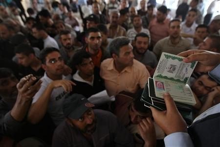 A Hamas policeman looks at the passports of Palestinians waiting to cross into Egypt at the Rafah border crossing in the southern Gaza Strip June 1, 2010. REUTERS/Mohammed Salem