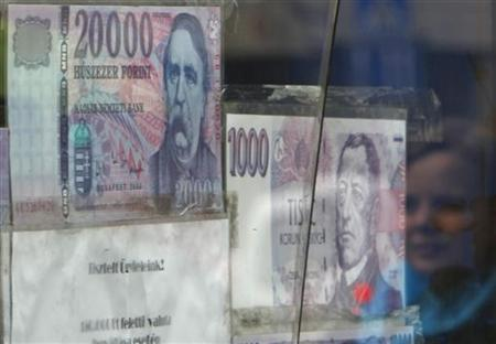 A woman walks past a money changer in Budapest on June 4, 2010. REUTERS/Laszlo Balogh