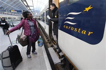 A passenger asks a Eurostar conductor for directions at St. Pancras International station in London February 11, 2010. REUTERS/Suzanne Plunkett