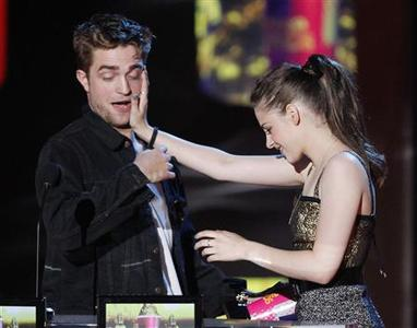 Actors Robert Pattinson and Kristen Stewart accept the award for Best Kiss as they attempt to kiss at the 2010 MTV Movie Awards in Los Angeles, June 6, 2010. REUTERS/Mario Anzuoni