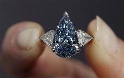 <p>An employee holds a rare 5.16-carat pear-shaped internally flawless fancy vivid blue diamond ring during a photocall at Sotheby's in London March 8, 2010. REUTERS/Andrew Winning</p>