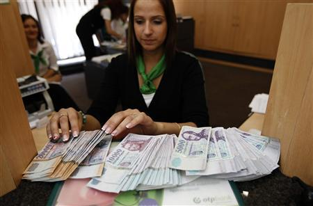 A clerk displays forint banknotes at Hungary's largest bank, OTP, in Budapest June 7, 2010. REUTERS/Laszlo Balogh