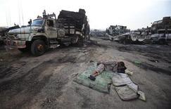 <p>Мужчина спит рядом с поврежденными грузовиками, которые подверглись атаке боевиков в пригороде Исламабада 9 июня 2010 года. По меньшей мере семь человек погибли и шесть ранены в пригороде Исламабада в результате обстрела неизвестными более 50 грузовиков, перевозивших грузы для сил НАТО в Афганистане, сообщила полиция. REUTERS/Faisal Mahmood</p>