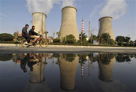Two men ride a motorcycle past a power plant in Xiangfan, Hubei province in this November 17, 2009 file photo. REUTERS/Stringer/Files