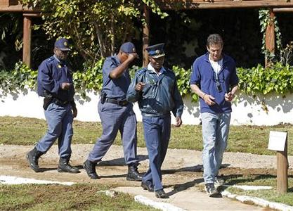 South African policemen walk with the manager (R) of the Nutbush Loma Lodge hotel, after an armed robbery to Portuguese journalists, in Magaliesburg June 9, 2010. REUTERS/Jose Manuel Ribeiro