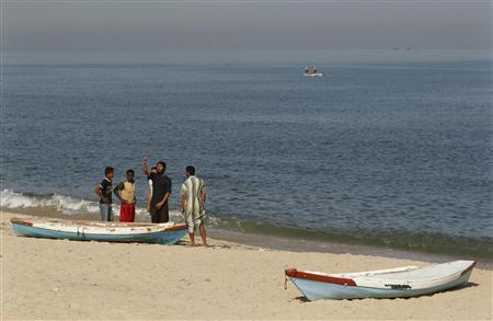 Palestinians stand next to a boat on a beach in the central Gaza Strip, June 7, 2010. REUTERS/Ibraheem Abu Mustafa