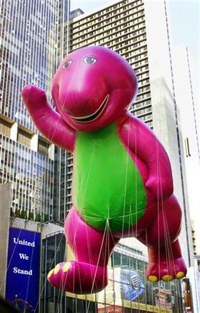 The Barney ballon waves to the crowds along Broadway during the 75th annual Macy's Thanksgiving Day parade, November 22, 2001 in New York City. REUTERS/Jeff Christensen