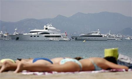 Sun bathers enjoy the weather in front of luxury boats moored in the Bay of Cannes May 15, 2008. REUTERS/Christian Hartmann