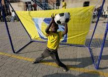 <p>Ребенок ловит мяч во время игры в футбол в центре Йоханнесбурга 4 июня 2010 года. Чемпионат мира по футболу 2010 года стартует в ЮАР 11 июня, и исход многих матчей турнира может быть решен в серии пенальти. REUTERS/Henry Romero</p>