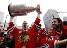 <p>Chicago Blackhawks' Patrick Kane (L) holds the Stanley Cup beside team-mate Adam Burish during a parade to honor the winners of the NHL's hockey championship in Chicago June 11, 2010. Two million fans turned out to celebrate the Chicago Blackhawks' National Hockey League championship with a ticker-tape parade on Friday, roaring their approval of the team's first Stanley Cup in half a century. REUTERS/John Gress</p>