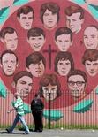 """<p>Люди проходят мимо стены, где нарисованы 14 жертв """"Кровавого воскресенья"""" 1972 года, Лондондерри 10 июня 2010 года. Премьер-министр Великобритании Дэвид Кэмерон извинился во вторник вечером за """"Кровавое воскресенье"""" - расстрел демонстрации ирландцев-католиков в 1972 году британскими войсками. REUTERS/Cathal McNaughton</p>"""