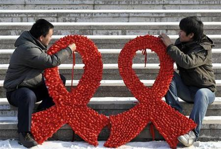 University students prepare large red ribbons on a street during an HIV/AIDS awareness rally ahead of World AIDS day in Shenyang, Liaoning province November 29, 2009. REUTERS/Sheng Li