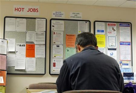 A job seeker reads the newspaper at The Work Place, which provides comprehensive employment and career services, in Boston, July 2, 2009. REUTERS/Brian Snyder