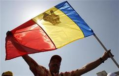"<p>A Romanian holds a national flag with a ""V"" sign drawn on it during a protest in front of Romania's Parliament palace in Bucharest June 15, 2010. REUTERS/Bogdan Cristel</p>"