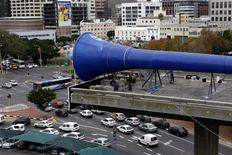 <p>Workers fix a giant vuvuzela soccer horn on top of Cape Town's famous unfinished highway bridge, May 27, 2010. REUTERS/Mark Wessels</p>