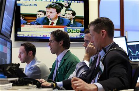 Specialist traders work on the floor of the New York Stock Exchange as a television broadcasts BP CEO Tony Hayward testifying before Congress June 17, 2010. Picture taken June 17, 2010. REUTERS/Brendan McDermid/Files